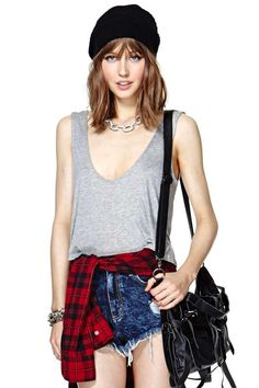 Grungy look. High waisted shorts, plain top, plaid shirt, beanie, over the shoulder bag.