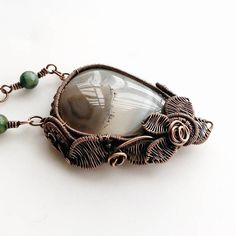 Wire wrapped botanical style Grey Crazy Lace Agate necklace. Pendant measurement: 5.5cmH x 4cmW, thickness 0.9cm. The necklace is a mixture of leather cord and African Turquoise beads, necklace length approximately 55.9cm (22 inches). The item is packed nicely in a gift box. When