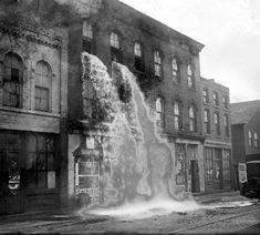Alcohol, discovered by Prohibition agents during a raid on an illegal distillery, pours out of upper windows of three-story storefront in Detroit, MI. 1929