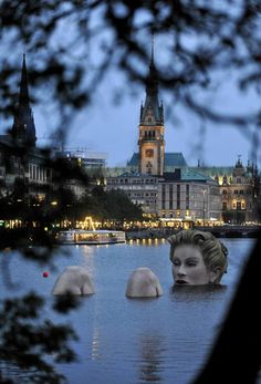 "A 'mermaid' sculpture created by Oliver Voss is seen in the late evening hours on Alster lake in Hamburg August 3, 2011. The four-metre-high sculpture dubbed ""Riesen-Nixe"" (grand mermaid) or ""Badenixe"" (bathing beauty) will be on display until August 12. REUTERS/Morris Mac Matzen (GERMANY - Tags: SOCIETY)"