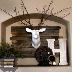 Rustic Industrial Mantle & Ceramic Deer Head Taupe walls in living room to compliment kitchen cupboards, wood beams and reddish fireplace stone Rustic Industrial Decor, Rustic Decor, Farmhouse Decor, Rustic Mantle, Industrial Decorating, Rustic Wood, Modern Farmhouse, Deer Head Decor, Stag Head