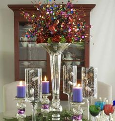 Shopping List for this display, the Christmas Table (see on Christmas board) and Thanksgiving Table (see on this board): 1 tall centerpiece vase, 6 mercury glass candlesticks, 3 footed hurricanes; 3 orange candles; 6 red pillar candles; 3 purple pillar candles; 3 branches of silk fall leaves; 250 peppermint sticks; 1 pound peppermint balls; 24 assorted glass ball ornaments; 8-10 sequined sprays.