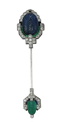 AN ART DECO SAPPHIRE, EMERALD AND DIAMOND JABOT PIN, BY CARTIER  Of palmette design, centering upon a carved oval-shaped cabochon sapphire, to the calibré-cut emerald half surround, with pavé-set diamond and black enamel detail, the opposing terminal set with a carved emerald in a calibré-cut sapphire and pavé-set diamond surround, 1930s, 10.5 cm, with French assay mark for platinum Signed Cartier Paris, no. 01229