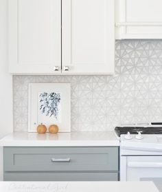 White and gray kitchen features white top cabinets and gray bottom cabinets paired with Caesarstone Pure White Quartz countertops and a white iridescent tile backsplash, Oceanside Glass Tessera Kaleidoscope Tiles.