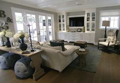 Style Network- Giuliana and Bill Rancic - Gorgeous living room with cream sectional sofa facing white built-in entertainment center over gray lattice rug. Additional living seating is composed of pair of brown leather ottomans and black and white wingback chair with Hermes Throw Blanket.