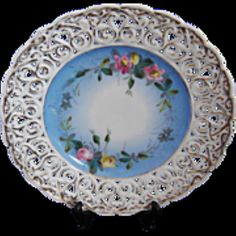 """For sale at Retrophoria.com, $50.00 - The central design is blue and white background with a delicate pink and yellow floral design and finally surrounded by gold trimmed reticular edge. The plate measures 9"""" across from edge to edge."""