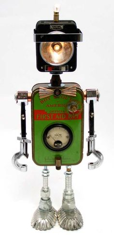 """Bright Boy"" Height: 17"" Principal Components: Boy scout first aid kit, flashlight, test tube clamps, volt meter, clock gear, hose fittings, tartlet tins Bright Boy's head does indeed light up--the bottom light in a steady beam, and the top light flashes."