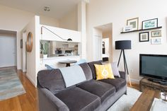 The living room and kitchen inhabit the same space, preserving the feel of a large, multi-purpose room of a school.