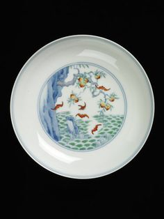 Dish | from Jingdezhen, China 1723-35 - The decoration on this dish is painted onto lustrous, honey-toned translucent porcelain, and consists of a peach tree growing from the side of a cliff and bats flying out to sea. The bat is synonymous with happiness, while the peach stands for longevity.