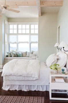 Inviting seaside bedroom... love the windows and inviting comfy window seat... wood beam ceilings and overstuffed white on white bed with just the right lighting for reading to the sound of the waves... sigh :)