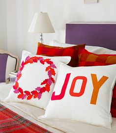 Cue the visions of sugarplums! Pillows with snipped-out and glued-on holly leaves and letters provide holiday cheer at bedtime. Using offbeat shades like mauve, rust, and ocher gives classic red and white a fresh twist. Learn how to make these pillows »   - CountryLiving.com