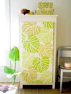 Dê uma personalidade ao armário, com uma fachada de grandes folhas tropicais. Pintadas em estêncil, sobre tela, as folhas são processadas em três tons de verde. Use o estêncil da folha em uma de cor, deixe secar, em seguida, reposicionar o estêncil, ligeiramente sobreposto ao primeiro e use outra cor. Transforme a tela em uma porta, prendendo ao armário com dobradiças e um botão de madeira pintada.