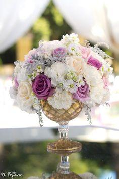 Hermoso centro de mesa con base dorada, elaborado en con rosas en tonos lilas, rosas y claveles blancos dándole un estilo vintage y romántico., desde Feztiva.com