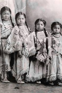 4 little Lakota girls (sisters perhaps) in traditional dress of their tribe (fringed, beaded hide dresses with matching leggings).
