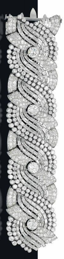 AN IMPRESSIVE ART DECO DIAMOND BRACELET The broad band composed of four pavé-set diamond scrolls, each centering upon a circular-cut diamond collet, flanked with baguette and circular-cut diamond scrolling lines, mounted in platinum, 1930s, 17.9 cm
