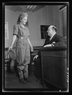 Safe clothes for women war workers. Correctly dressed, correctly coiffed and ready for work, Eunice Kimball shows her new safety uniform and hair-do to Bendix's chief inspector, Walter Rodgers, who thoroughly approves the transformation. In compliance with all safety rules, her uniform is also smart-looking and washable besides. Note that she wears her identification badge at the belt. Bendix Aviation Plant, Brooklyn, New York Photographer Ann Rosener Created March 1943