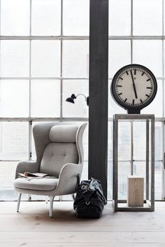 Modern take on a traditional arm chair, oversized clock, simple chunk of wood as accessory. Log, rustic Ro by @Daniel Morgan Vasey of Fritz Hansen  #interiors #window