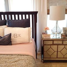 Master bedroom combining moody navy blue, blush pink, & grey bedding with mirror side table & mercury glass lamp.