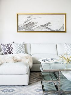 Bright living room with a light gray sectional, a glass coffee table and abstract throw pillows