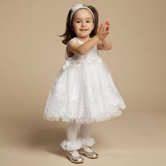 Baby girls white tulle ruffle dress and headband by Couche Tot. This very pretty set comprises of a sleeveless satin bodice with a pleated organza overlay and peter pan collar with a ribbon and diamanté bow in the centre. The waistband is decorated with satin and grosgrain ribbon bows with diamanté and pearl centres. The skirt has a tulle overlay with lace embroidery and layers of fluted tulle ruffles, a satin underskirt and tulle petticoat, which adds fullness. It has a smooth lining and…