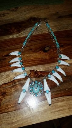 One of a kind Squash Blossom, made with natural untreated Burtis Blue Turquoise, Buffalo teeth and sterling silver.  www.facebook.com/beautifulturquoisestones     Deigned by, Clint Cross    Made by,  Fierro