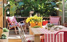 Utilizada para refeições mais demoradas e especiais, a mesa de jantar da área externa tem cadeiras de latão com almofadas florais. A caixa de vinho virou cachepô para as tulipas. Casa da produtora de eventos Lica Paludo
