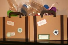 Cardboard suitcases double as decorations and party favor bags for an airplane/flight/travel party.