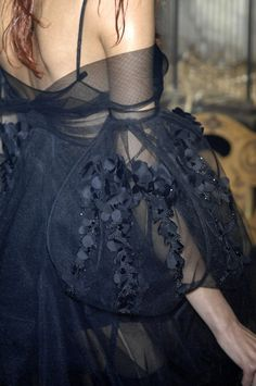 Dark Romance: voluminous sleeve with delicate floral appliqué on sheer fabric; close up fashion details