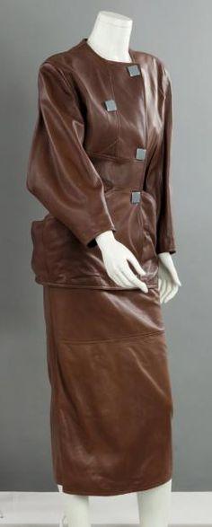 Anne-Marie BERETTA, circa 1986/1989 Veste longue en cuir cognac à encolure ronde, double boutonnage pressions agrémenté de boutons façon aluminium, manches longues, effet de découpes dont une soulignant les poches décollées, jupe mi-longue à l'identique. Griffe blanche, graphisme marine.