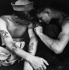 Dec 1944 aboard the USS Pacific Ocean. A sailor inspects the tattoo of a fellow gob.