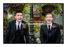 Groom and bestman checking out the summer flowers