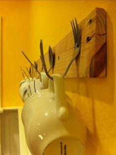 Coffee mug display using old forks and spoons.