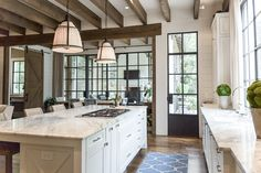 Kitchen with beams and iron windows and doors: PRITCHETT+DIXON