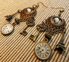 Steampunk Brass Clockfaces, Victorian Key, and Eiffel Tower Charms, Filigree with Cats Eye Beads Dangle Earrings Perfect for a Hugo Fan. $24.95, via Etsy.