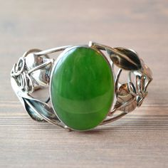 Siberian Jade Cuff - This gorgeous piece of Jade has a great olive tone and it is surrounded in elegant silver calla lilies and leaves. www.villagesilversmith.net