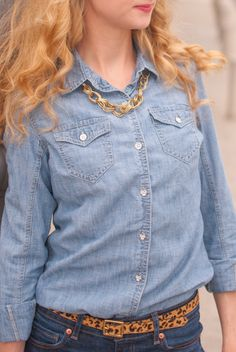 A simple gold chain necklace really stands out on a light denim shirt.