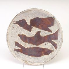 """PETER VOULKOS Unusual stoneware plate incised with three stylized birds in flight, in leathery matte brown glazes against a light gray ground. A few hairlines, some restored. Incised """"Voulkos""""."""
