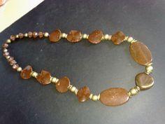 Colar com contas de resina marrom e peças de metal em ouro velho.