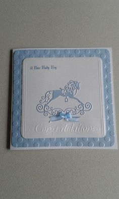 Baby boy card. This 8inch square card features a tattered lace rocking horse die cut fom pearlescent card.