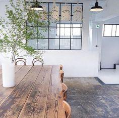 verrière intérieure, grande table en bois rustique et lampes industrielles