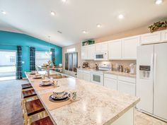 Clean white cabinets are complimented by vivid blue accents. Love the counter-height island breakfast bar! Highland Homes' Serendipity model home in Davenport, Florida.