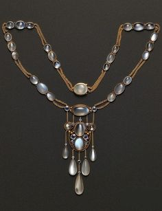 Arts & Crafts Moonstone and Sapphire Pendant Necklace, attributed to F.G. Hale, the wirework pendant with bead motifs bezel-set with cabochon oval and circular moonstones and circular-cut sapphires suspending a fringe, suspended from a conforming necklace, joined by delicate curb link chain, gold mount, unsigned. #Hale #ArtsCrafts #vintage #moonstone #necklace
