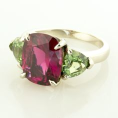18KT white gold three stone ring set with one center 4.85ct. cushion cut rubellite tourmaline, and two (2) trillion shaped apple green tourmalines weighing 2.08cts.