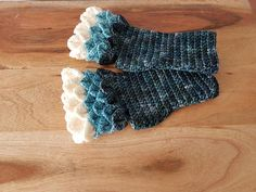 These gorgeous mermaid inspired fingerless mitts will fit size small and medium hands. I have used high end yarn that is very soft and also unusual vibrant colours. The first scale is a white, the second is aqua and the third a variated navy blue yarn. This high end yarn is hand dyed and therefore the colours have a watercolour effect.  These are great for people that work with their hands and need the use of their fingers, for driving in cold weather, for people that want a little warmth…