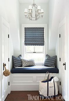 Simple, blue and white geometric patterned pillows and curtains in a coastal home