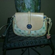 Dooney & Bourke crossbow handbag A multi colors trim with tan leather handbag that measure about 5 ins from top to bottom and 8 ins from side to side and adjustable shoulder strap has small sign of soil no rips or tears has small sign of water spots on good used condition. Dooney & Bourke Bags Crossbody Bags
