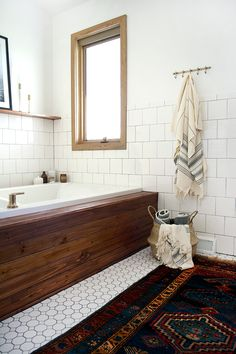 Modern Vintage Bathroom Makeover, large dark rug, white square tile, wooden bath surround