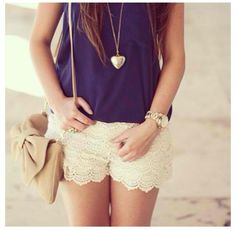 Navy blue shirt, white lace shorts, heart necklace and a nude color purse.
