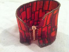 This cuff is inspired by the amazing work of artist Scott McMillan - his piece is composed of recycled auto parts! The luscious blends of colors are a combination of silver lined and transparent glass. The gradations are from a deep purple to a burnt orange. The clasp is sterling silver, attached with transparent red beads. Copper tones in the edging beads further complement the