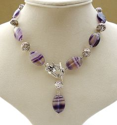 This is a reserved listing for Suzanne, and includes a matching pair of purple fluorite drop earrings. This unique design gemstone necklace showcases beautiful striped purple fluorite ovals. The stripey purple fluorite is alternated with decorative silver tone Bali Style beads, linked together rather than strung. The unusual but pretty design features a floral toggle clasp in the Art Nouveau style, which fastens at the front. Hanging from the clasp is a fluorite and silver metal bead charm